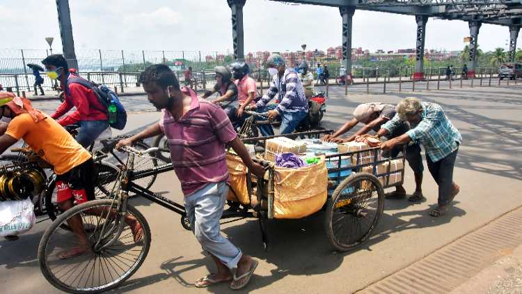People travel by road as the government suspended local trains and bus services amid the rise in COVID-19 cases, in Kolkata on Thursday