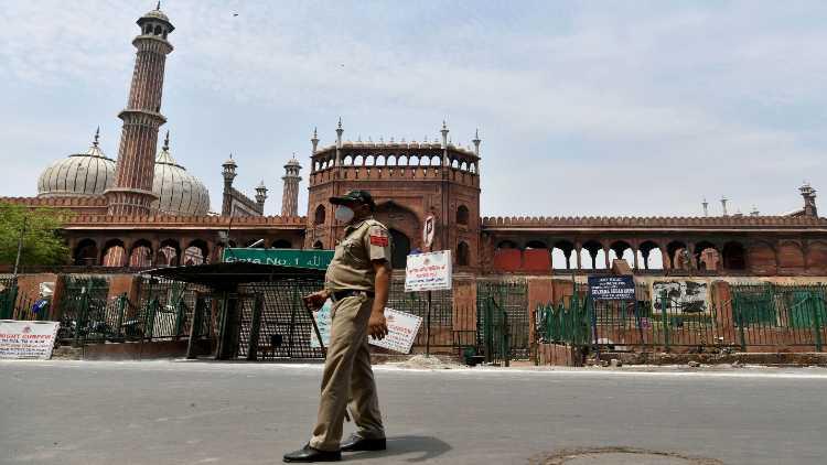 A Delhi Police personnel patrols outside the deserted Jama Masjid