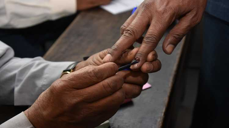 A polling official applies indelible phosphorus ink on the fore finger of a voter