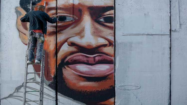 Palestinian artist Taqi Spateen paints a mural of George Floyd