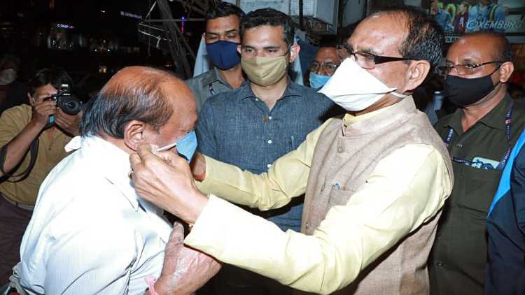 Madhya Pradesh CM Shivraj Chauhan offers a mask to a person
