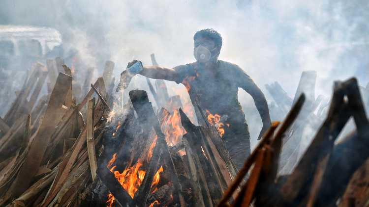 Relatives perform the last rites of a COVID-19 victim during mass cremation at Ghazipur crematorium in New Delhi on Saturday